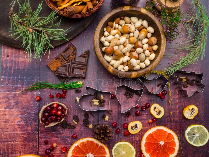 Holiday food background for baking cookies with cutters, spices, fruits, cranberries, nuts, dried apples, chocolate, raisin, on royalty free stock photography