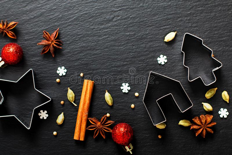 Holiday Food background Christmas cookies cutter spices Star anise, cloves and cadamon pods on black slate board royalty free stock photos