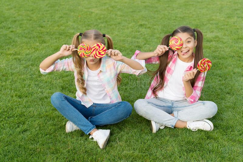 Holiday food. Sweet childhood. Happy children hold candy sit green grass. Candy shop. Lollipop treats. Candy synonym for. Happiness. Sugar and calories. Joyful royalty free stock photos