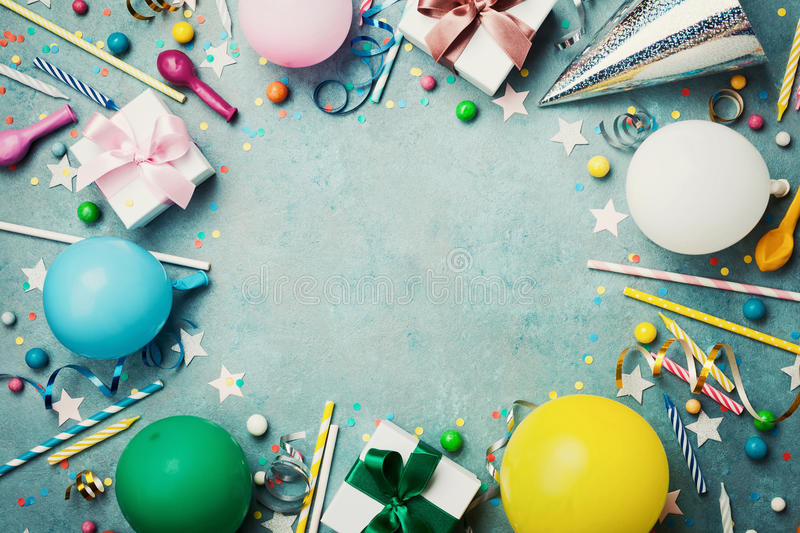 Holiday frame or background with colorful balloon, gift, confetti, silver star, carnival cap, candy and streamer. Flat lay style. Birthday or party greeting royalty free stock images