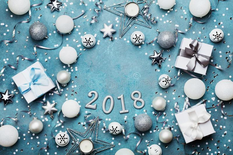 Holiday frame with christmas decoration, gift box, confetti and sequins on vintage blue table top view. Flat lay. New year 2018. stock image