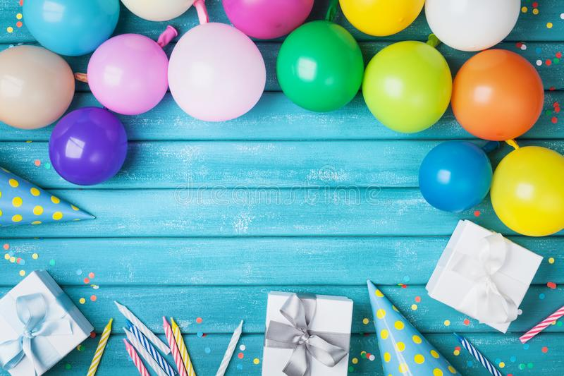 Holiday frame with colorful balloons, gifts, confetti and carnival cap on turquoise table top view. Birthday or party card. stock photography