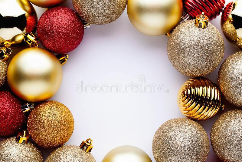 Holiday frame made of stylish Christmas shiny golden and red balls or bauble on white background royalty free stock photos