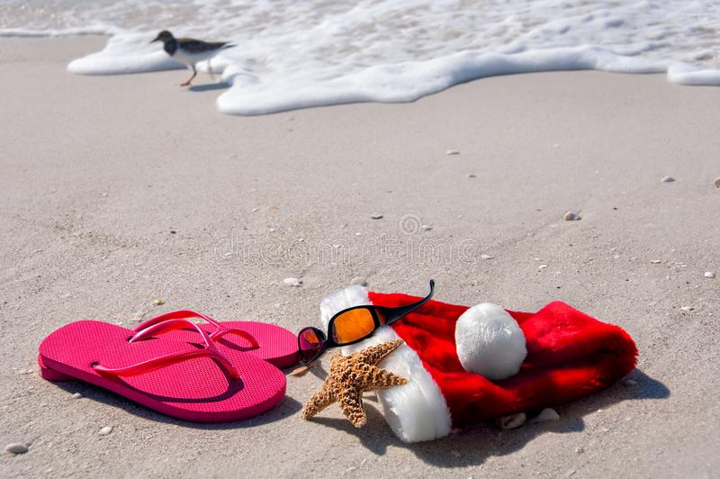 Holiday fun at the beach. Tropical Christmas at the beach, with flip flops, sunglasses, a starfish and santa hat stock image