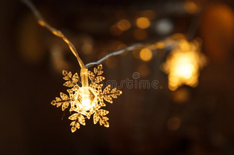Holiday garland, clear plastic snowflake glows with a Golden light. Christmas lights, creating a festive mood. Close-up shot stock photos
