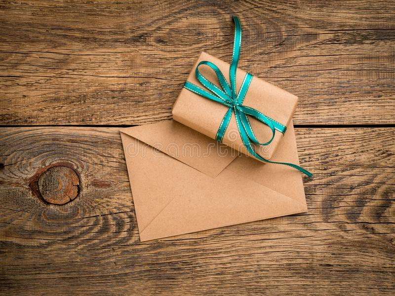 holiday gift box, tied with green ribbon, envelope of Kraft paper, blank on the wooden weathered rustic background, top view. royalty free stock images