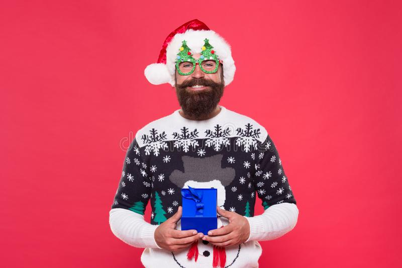 Holiday gift delivery. Happy santa hold christmas gift. Bearded man got gift red background. Holiday gift. Christmas and. New Year celebration. Shopping stock photo