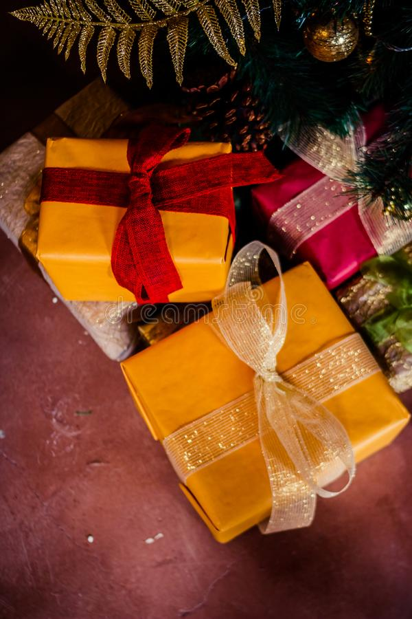 Holiday gift under Christmas tree wrapped with twine and wrapping paper decorated with garland lights and toys.Holiday royalty free stock images