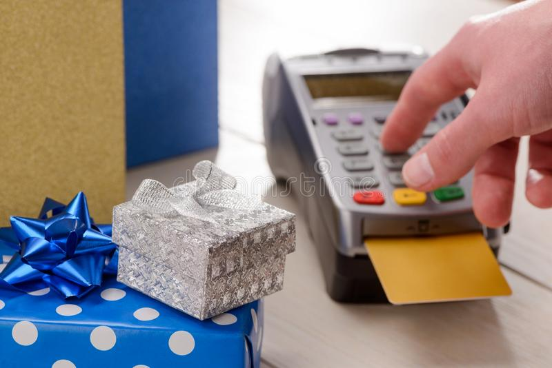 Holiday gifts in the foreground. Customer entering a PIN code on a terminal with inserted credit card stock photo