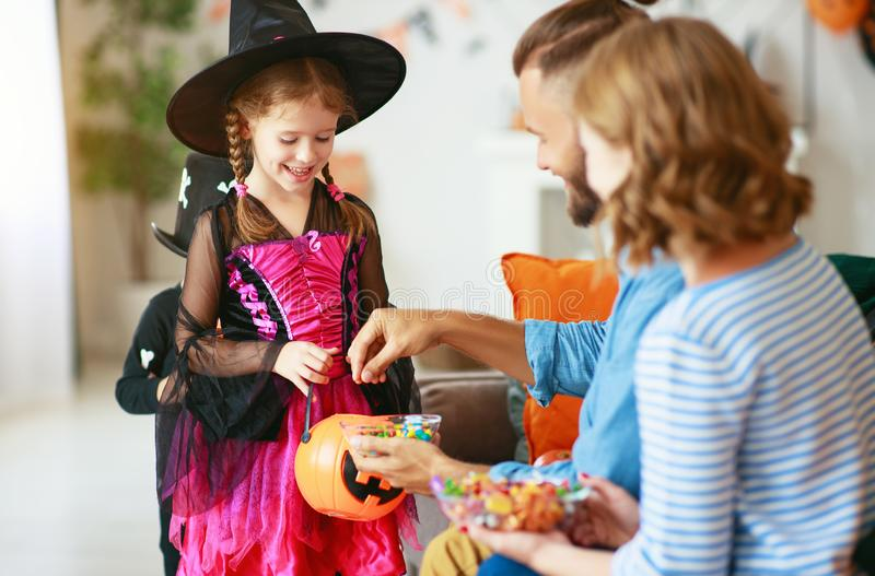 Holiday  Halloween. children ask their parents for candy in costumes. Holiday of Halloween. children ask their parents for candy in costumes royalty free stock images