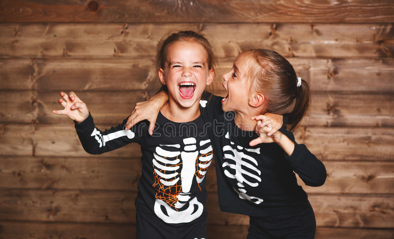 Holiday halloween. funny funny sisters twins children in carnival costumes skeleton on wooden . Holiday halloween. funny funny sisters twins children in royalty free stock image