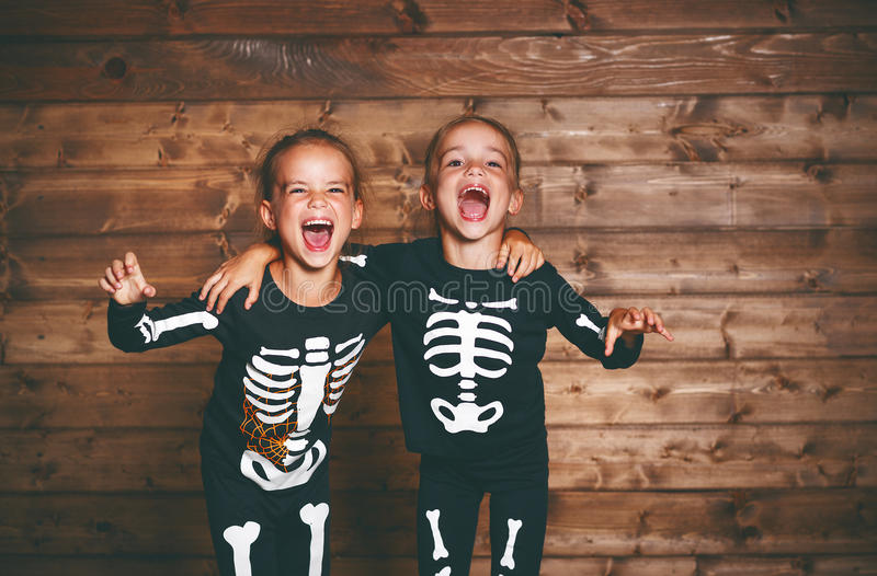 Holiday halloween. funny funny sisters twins children in carnival costumes skeleton on wooden. Holiday halloween. funny funny sisters twins children in carnival stock images
