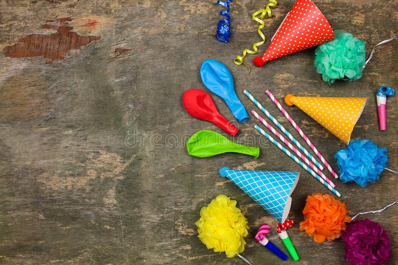 Holiday hats, whistles, balloons on old wooden background. stock images