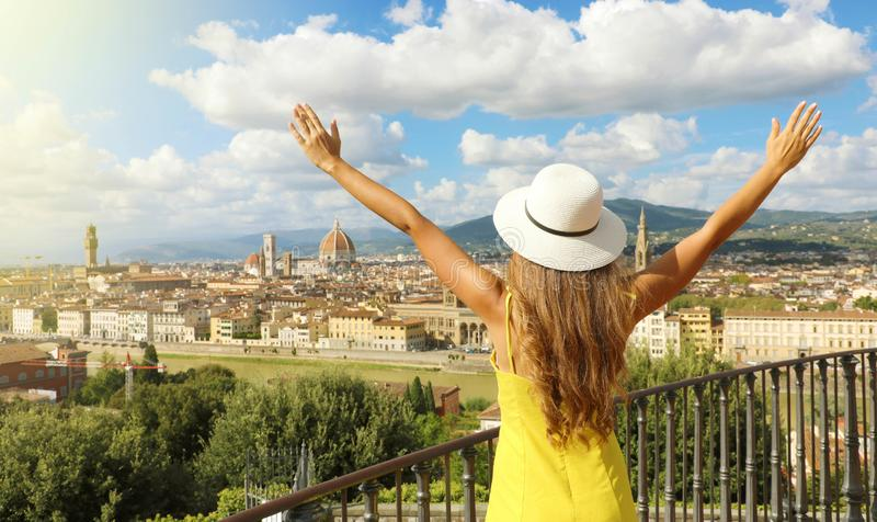 Holiday in Italy. Panoramic back view of young woman with hat and raised arms looking at Florence city, Tuscany, Italy royalty free stock photos
