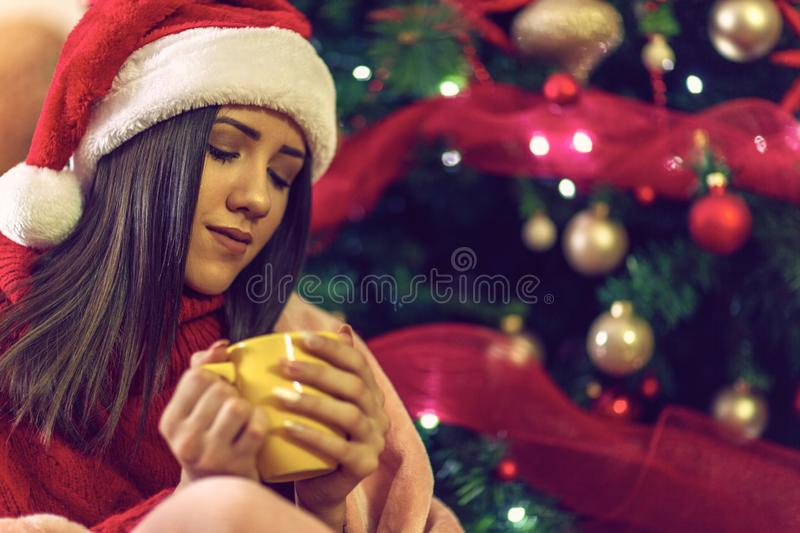 .Holiday joy. woman holding a cup on christmas at home stock photo
