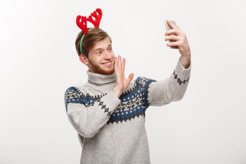 Holiday and lifestyle concept - Young handsome beard man taking a selfie or talking facetime with friend. royalty free stock photography