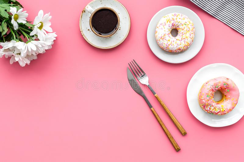 Holiday lunch for woman with cup of americano, donut and flowers on pink background top view mock up stock photography