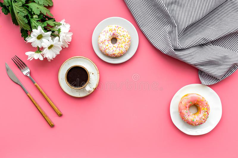 Holiday lunch for woman with cup of americano, donut and flowers on pink background top view mock up royalty free stock photo