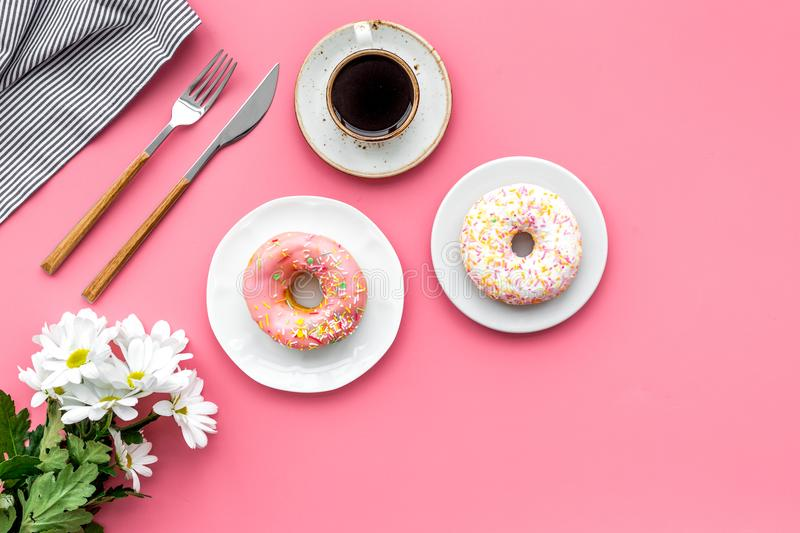 Holiday lunch for woman with cup of americano, donut and flowers on pink background top view mock up stock photos