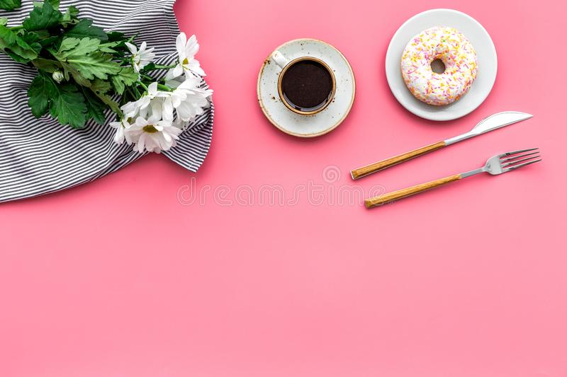 Holiday lunch for woman with cup of americano, donut and flowers on pink background top view mock up royalty free stock photography