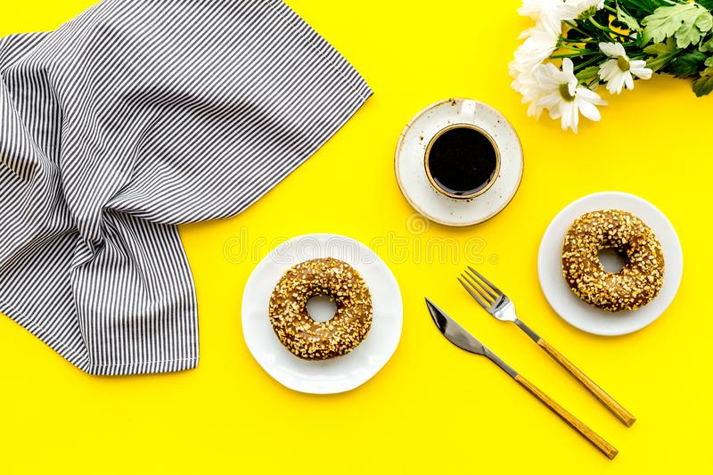 Holiday lunch for woman with cup of americano, donut and flowers on yellow background top view royalty free stock photography