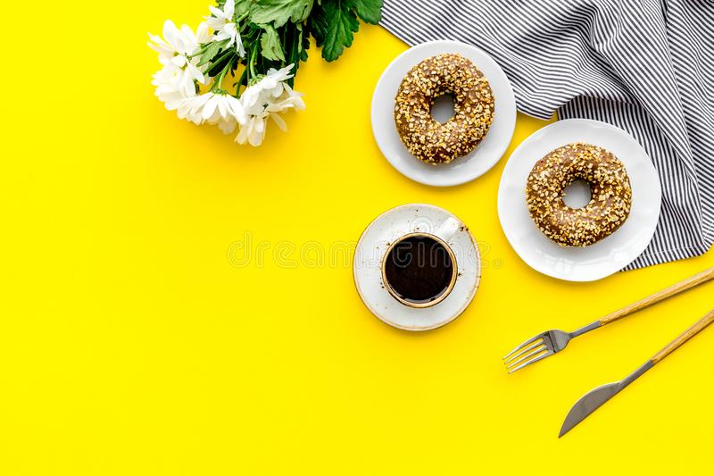 Holiday lunch for woman with cup of americano, donut and flowers on yellow background top view mock up stock image