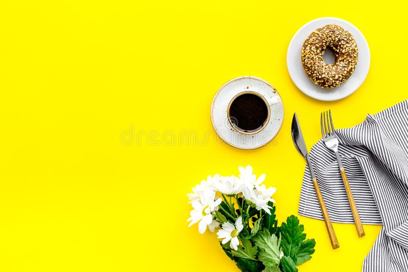 Holiday lunch for woman with cup of americano, donut and flowers on yellow background top view mock up royalty free stock images