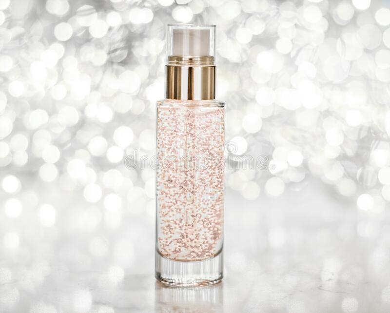 Holiday make-up base gel, serum emulsion, lotion bottle and silver glitter, luxury skin and body care cosmetics for beauty brand. Cosmetic branding, blank label stock photo