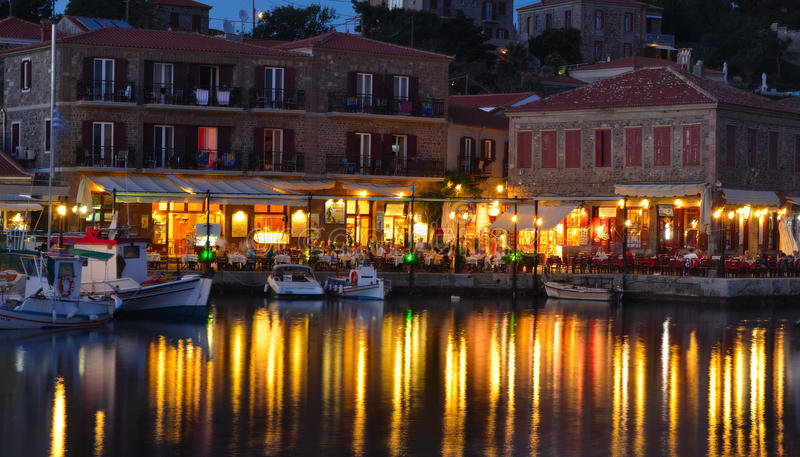 Holiday makers dining in harbor side restaurants Molyvos Greece. MOLYVOS, LESVOS, GREECE - JUNE 12, 2014: Holiday makers dining in harbor side restaurants royalty free stock photo