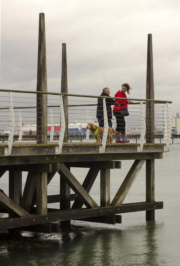 Holiday makers and their dog on the viewing platform pier overlooking the Southampton Water at Hythe in Hampshire on the south coa. Holiday makers and their dog stock images
