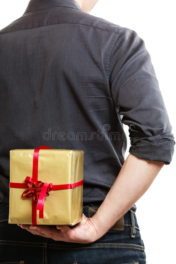 Holiday. Man hiding surprise gift box behind back royalty free stock photo