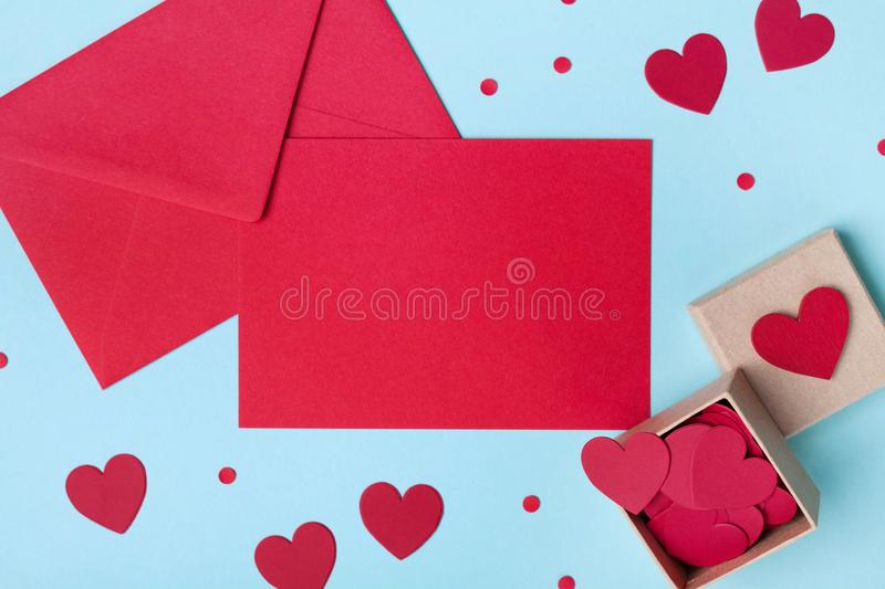 Holiday mockup for Valentines day. Box full of red hearts and paper card with envelope on blue table top view. Flat lay style. stock photos