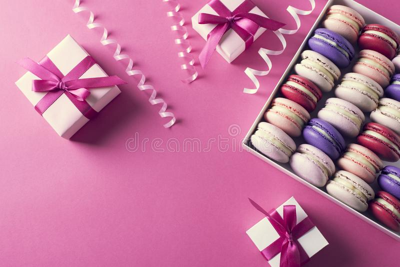 Holiday mood with gift boxes and colored sweet macaroons stock photography