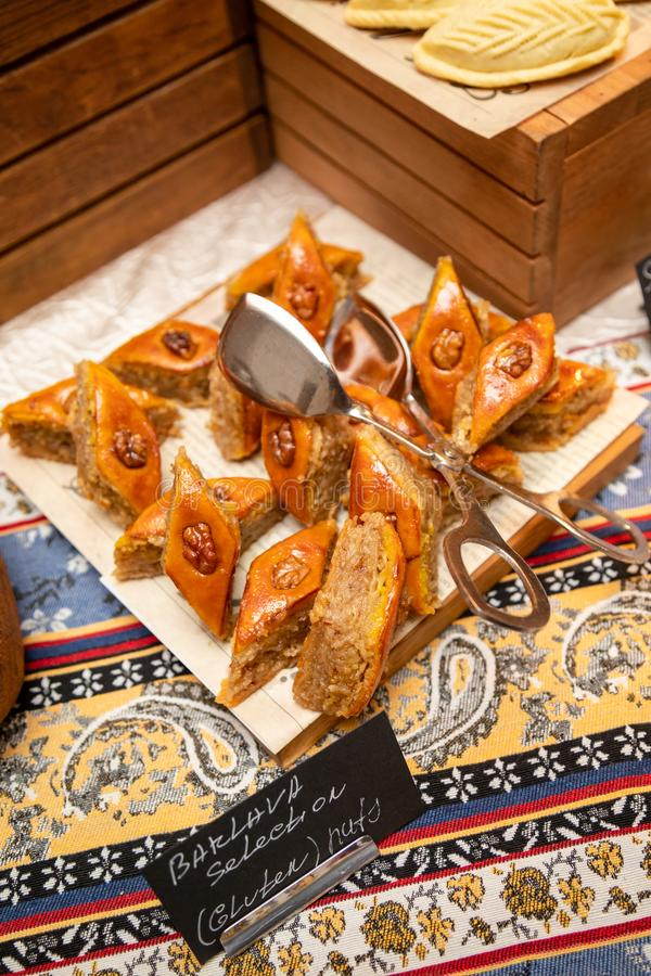 The Holiday Of Navruz. National color.A traditional dish of pakhlava dough.On a brown wooden plate on a silk scarf with a national. Print Buta royalty free stock photography