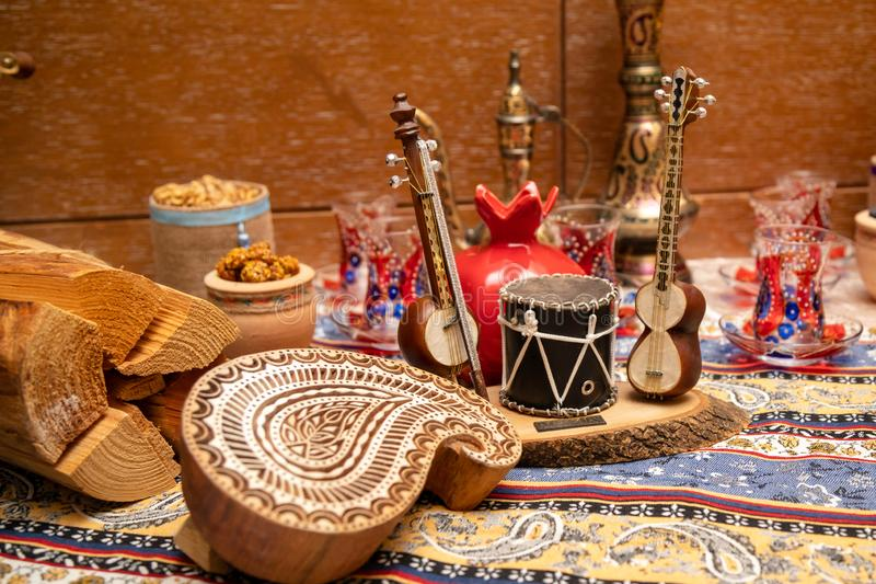 The Holiday Of Navruz.Small figures of national musical instruments: tar, drum on a wooden stand, on the background of tea glasse. S in the form of pears, old royalty free stock photos