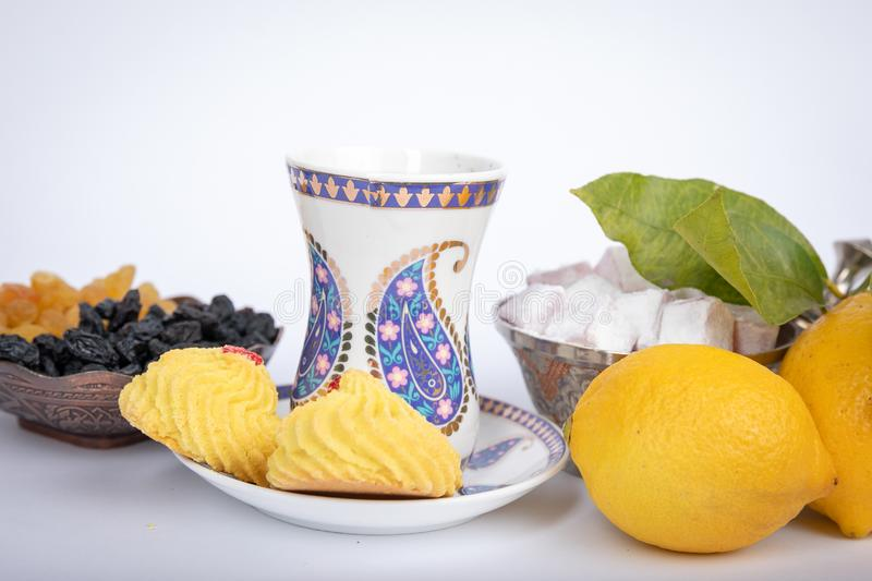 The holiday of Navruz. Traditional armudu tea Cup with national patterns and buta print. Two lemons with a branch, Turkish delight, black and white raisins in stock images