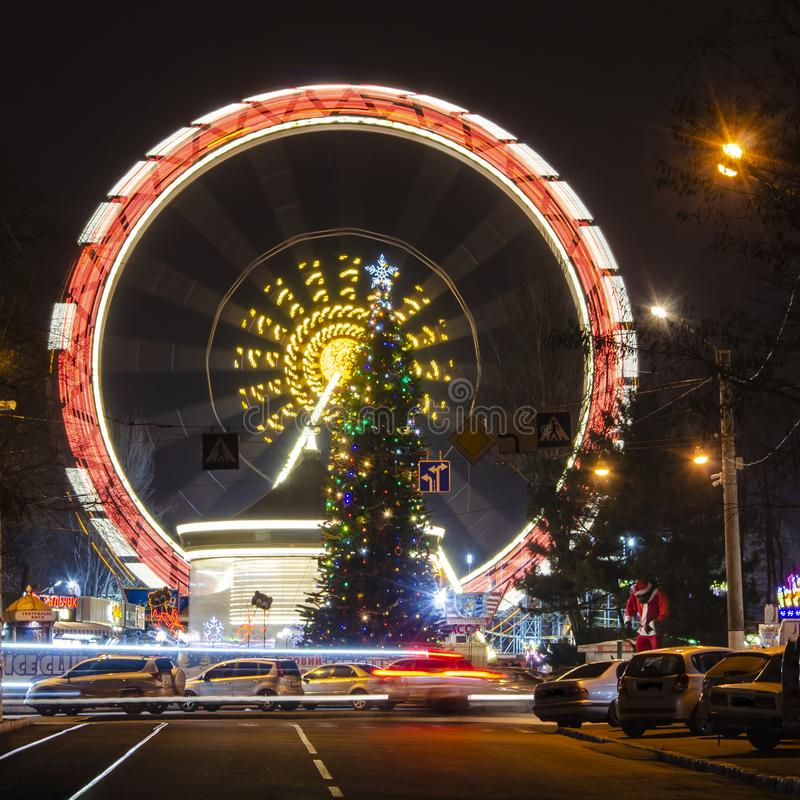Holiday New year, colorful lights on a Christmas treeOdessa city, Ukraine. Holiday New year, colorful lights on a Christmas tree and a ferris wheel.Odessa city stock photography