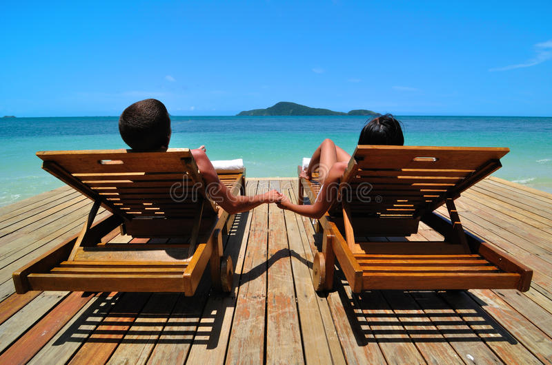 Holiday in Paradise. A couple sunbathe at a tropical resort