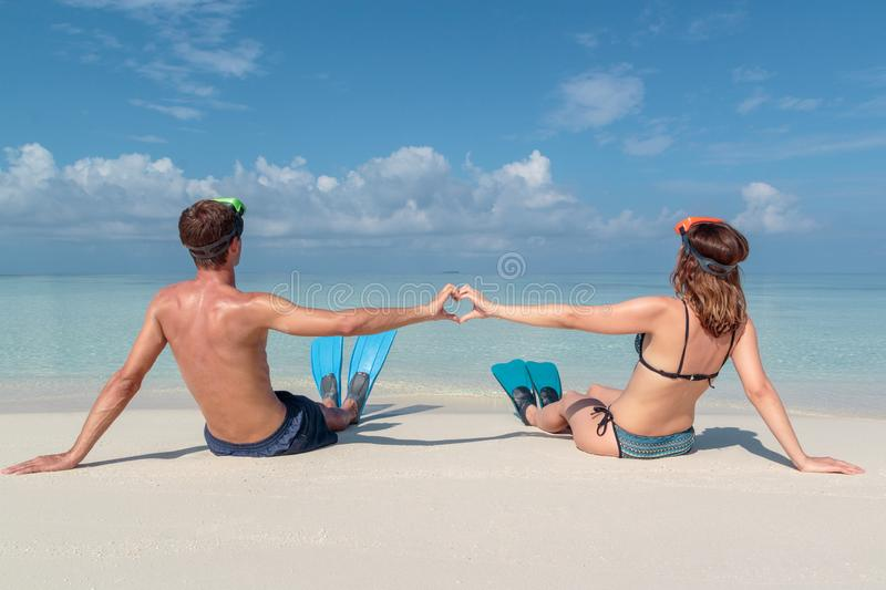 Picture from back of a young couple with flippers and mask seated on a white beach in the Maldives. Crystal clear blue water as stock photography