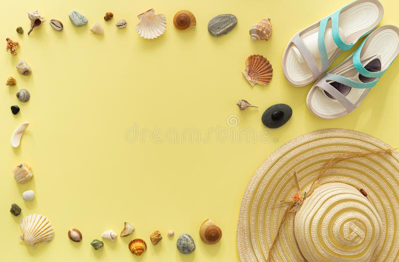 A holiday photo, a summer hat, beach sandals, sunscreen, sun glasses, scallops and souvenir pebbles.  Empty space for an inscripti. On / yellow background stock image