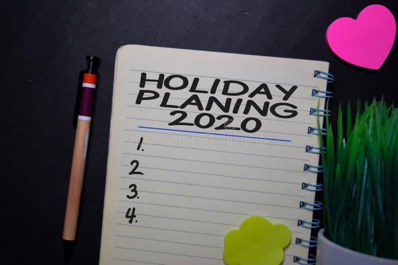 Holiday Planning 2020 escribir en un libro aislado en una tabla negra imágenes de archivo libres de regalías