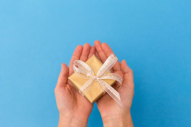 Hands holding small christmas gift box. Holiday, presents and greetings concept - hands holding small christmas gift box on blue background stock image