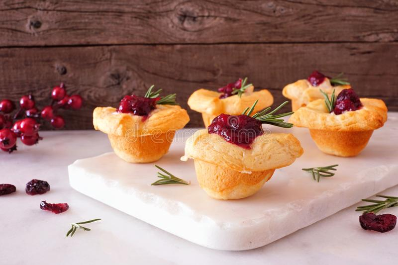 Holiday puff pastry appetizers with cranberries and baked brie, side view platter stock photo