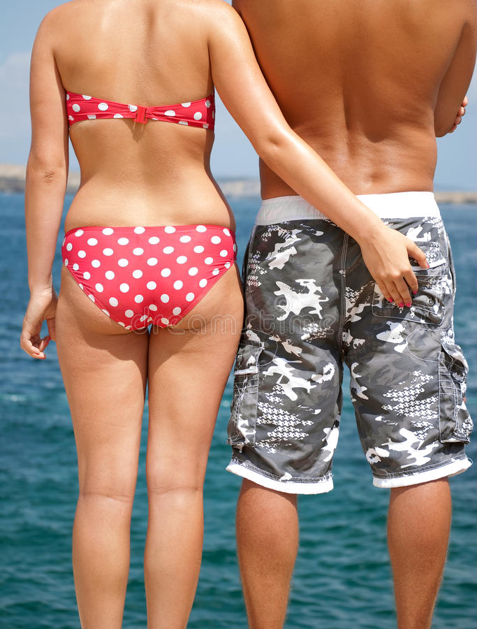 Holiday romance. Girl pinching mans by the sea royalty free stock photo