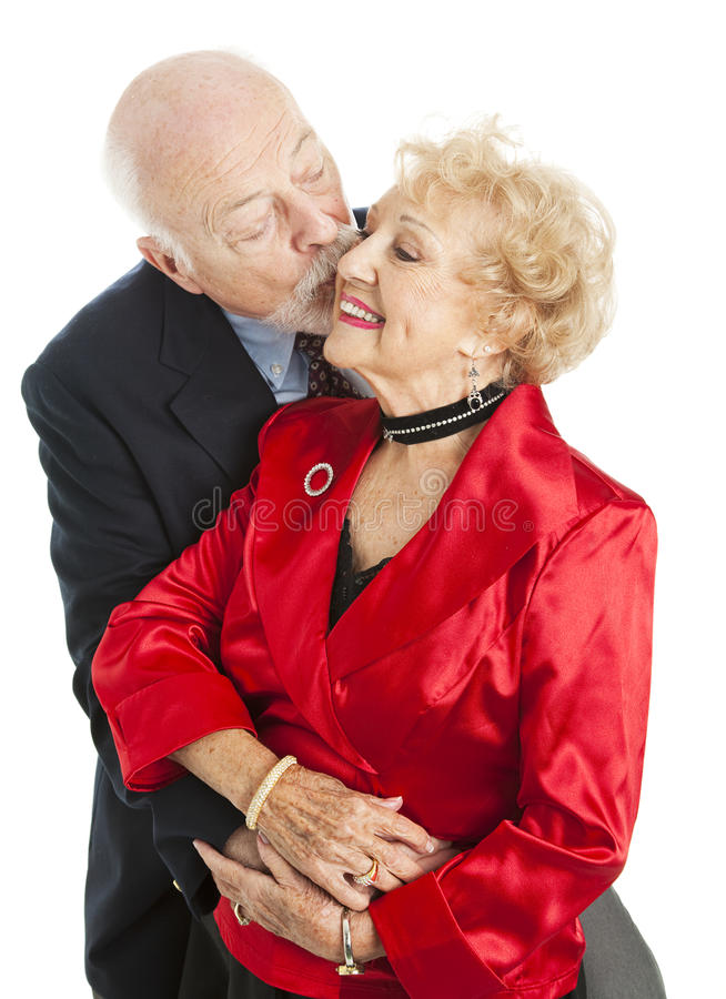 Holiday Seniors - Kiss for Her. Senior couple dressed for the holidays. He's giving her a kiss on the cheek. Isolated stock photo