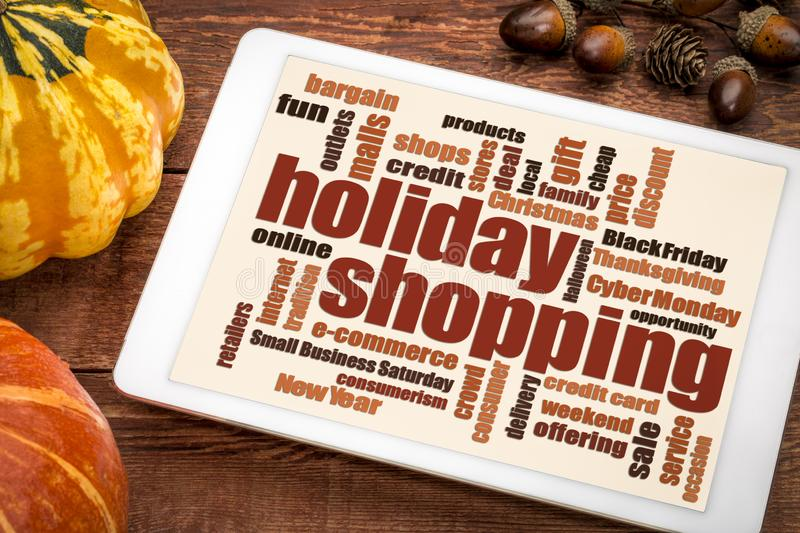 Holiday shopping word cloud. On a digital tablet with a pumpkin and gourd royalty free stock photo