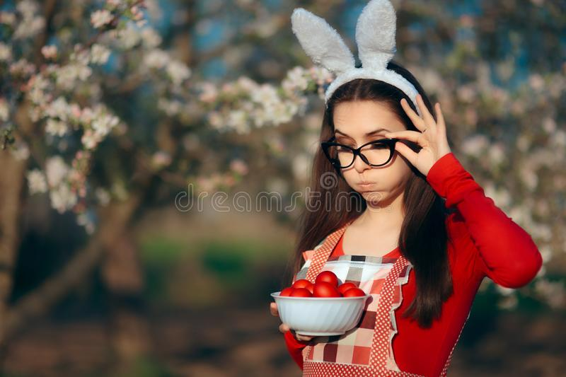 Funny Tired Housewife with Bunny Ears, Apron and Easter Eggs stock photography