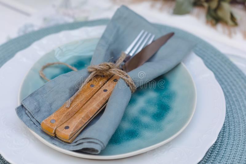 Holiday Summer or early autumn outside table setting with linen napkins and green leaves. Close up. Holiday Summer or early autumn outside table setting with royalty free stock photos