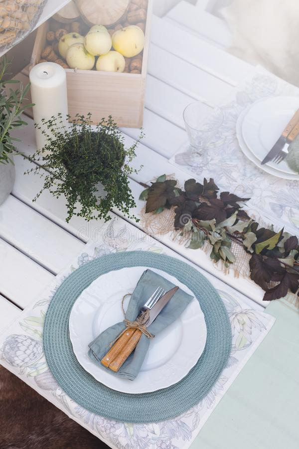 Holiday Summer or early autumn outside table setting with linen napkins and green leaves. Close up. Holiday Summer or early autumn outside table setting with stock photo