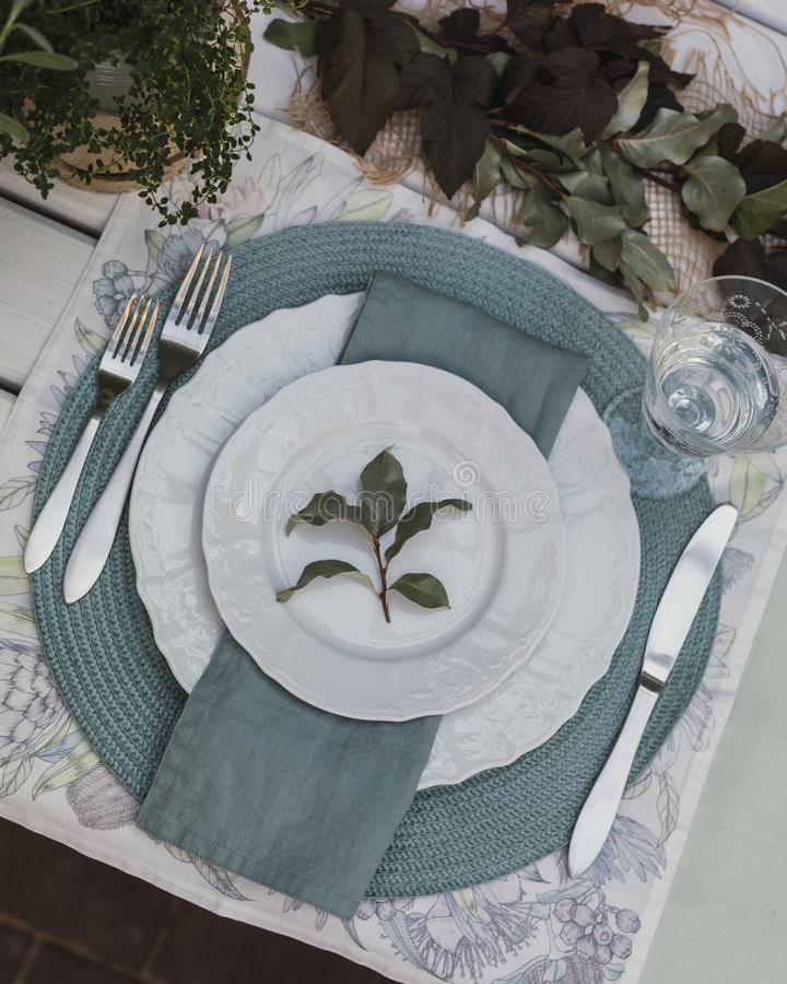 Holiday Summer or early autumn outside table setting with linen napkins and green leaves. Close up. Holiday Summer or early autumn outside table setting with stock photography